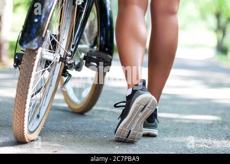 Jambes de jeune femme en forme de vélo dans un parc de la ville
