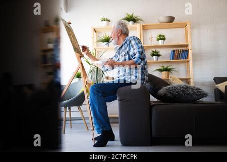 Joyeux homme retraité peint sur toile pour s'amuser à la maison Banque D'Images