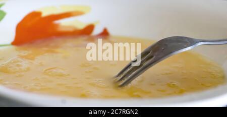 Gros plan d'une fourchette et de jaunes d'œufs battus pour une omelette Banque D'Images
