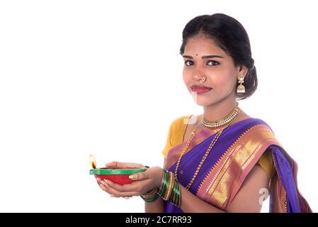 Portrait d'une femme tenant une photo de diya, Diwali ou deepavali avec des mains de femmes tenant une lampe à huile pendant le festival de lumière sur fond blanc Banque D'Images