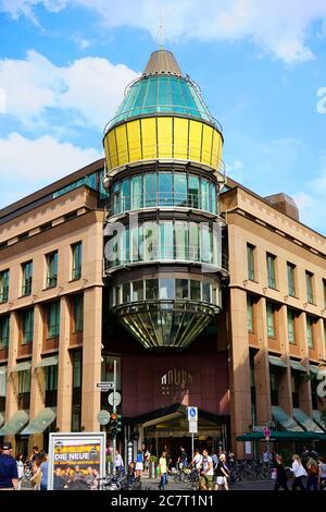 Vue extérieure de la façade moderne du centre commercial 'Schadow-Arkaden', pendant une journée d'été chargée. Le centre commercial a ouvert ses portes en 1994.