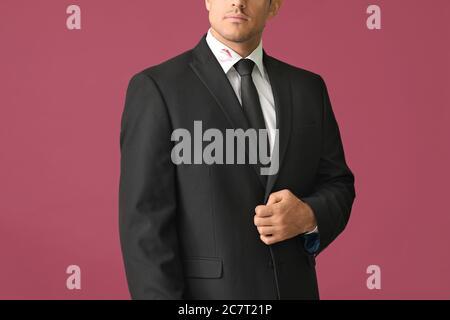 Jeune homme d'affaires avec imprimé lèvres sur le col de chemise sur fond de couleur Banque D'Images