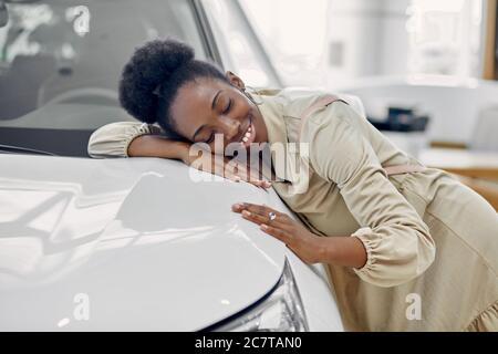 belle femme afro rêve de nouvelle voiture, jeune femme est venue voir des automobiles, faire l'achat. femme est penchée sur la voiture blanche luxueuse, souriant