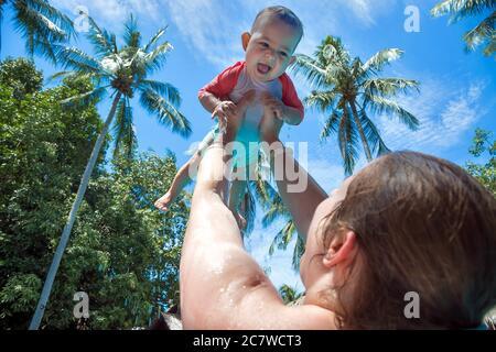 Maman a élevé l'enfant au-dessus de la tête dans la piscine. La petite fille est très heureuse et crie pour la joie. Vacances d'été, palmiers et ciel bleu sur le fond. Banque D'Images