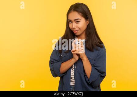 Portrait de la jeune fille sournoise dans une chemise en denim qui fume et pense à l'idée de ruse, planifiant le mauvais prank, méchant vengeance, gesticulant avec un regard avide Banque D'Images