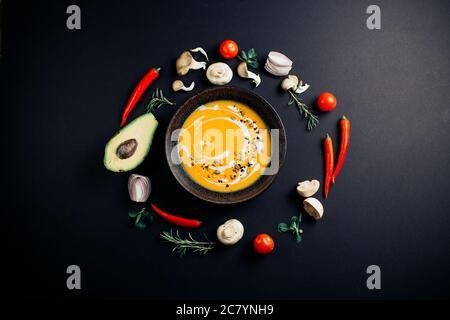 Soupe de potiron parmi les feuilles d'automne sur un background.frame noir d'avocat, champignons, tomates, oignons, Chili et verts Banque D'Images