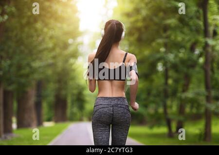 Vue arrière de la Sporty Fit Jeune femme jogging dans le parc de Green City