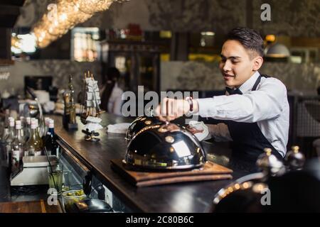 Young waiter in tuxedo holding plateau avec cloche métallique et une serviette