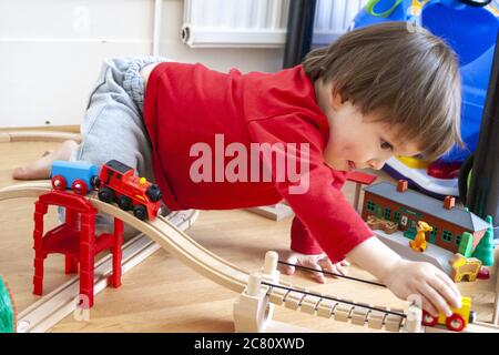 Caucasien enfant, de 3-4 ans, à l'intérieur. Niveau du sol Vue de jeune garçon jouant avec Thomas réservoir du moteur de la rame. La poussant le long de la piste.