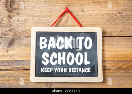 RETOUR À L'ÉCOLE GARDEZ VOTRE MESSAGE TEXTE DE DISTANCE sur un tableau noir, fond de mur en bois, propagation du coronavirus dans la mesure de prévention scolaire Banque D'Images