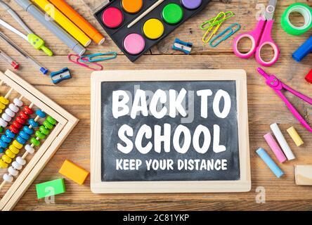 RETOUR À L'ÉCOLE GARDEZ VOTRE MESSAGE TEXTE DE DISTANCE sur un tableau noir, fournitures scolaires fond, propagation du coronavirus dans la mesure de prévention scolaire Banque D'Images