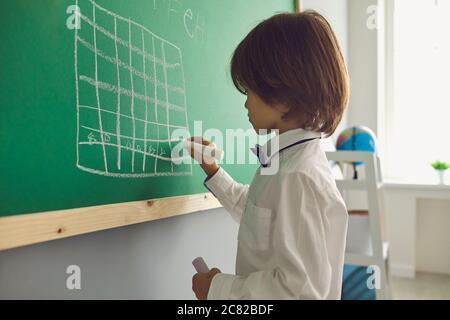 Leçon d'échecs pour les enfants. Garçon dessine un échiquier sur le tableau vert dans la salle de classe. Banque D'Images