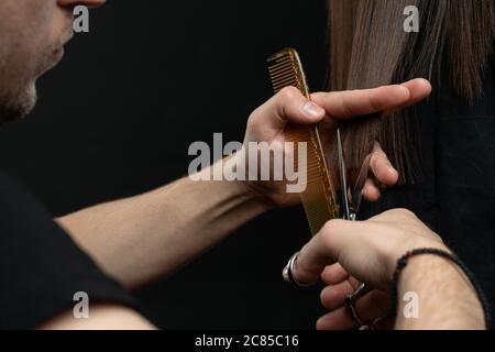 Un gros plan de coiffeur mains couper les cheveux, coiffeur avec le client