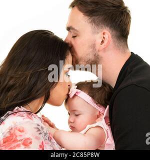 Portrait carré de style de vie d'un jeune couple avec leur fille à son premier anniversaire. Banque D'Images