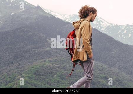 Sac à dos rouge avec l'homme de marcher seul dans les montagnes. Style de voyage adventure concept Banque D'Images