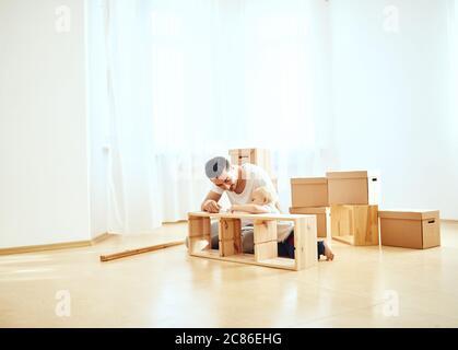 Père et petit fils assemblant des meubles à la maison Banque D'Images