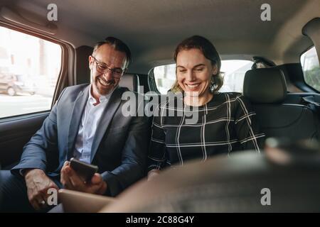 Femme d'affaires travaillant sur un ordinateur portable avec un homme d'affaires utilisant un téléphone mobile lors de voyages en voiture. Les gens d'affaires travaillant à l'arrière du taxi.