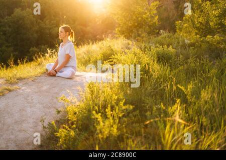 Paix et tranquillité complètes jeune femme méditant assis en position lotus avec les yeux fermés