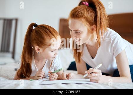 Jolie petite fille avec queue de cheval au gingembre allongé sur le lit avec sa mère et utilisant des crayons de couleur pour faire une carte de Noël, intérieur de salon confortable o