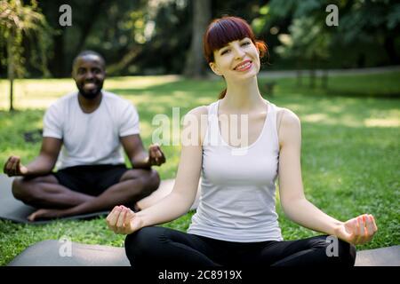 Vue de face d'un couple multiethnique pratiquant le yoga dans le parc. Souriante jolie femme caucasienne assise dans lotus poser sur le tapis. Homme africain joyeux