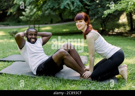 Fitness, sport, entraînement, travail d'équipe et concept de personnes. Beau homme africain musclé, faisant des places assises dans le parc vert d'été avec son entraîneur personnel Banque D'Images