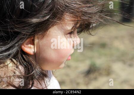 Portrait de profil et gros plan de la magnifique petite fille avec des cheveux longs et flambants sur un arrière-plan extérieur flou Banque D'Images