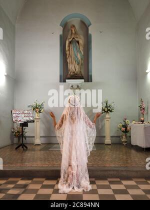 Portrait vertical d'une femme debout et priant dans une église Banque D'Images