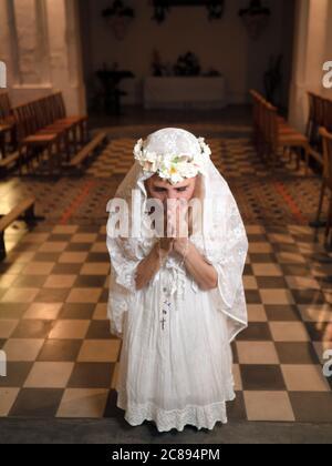 Portrait vertical d'une femme s'agenouillant et priant dans une église avec un rosaire Banque D'Images