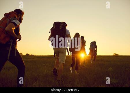 Randonnée. Randonnée. Tourism.UN groupe de touristes avec des sacs à dos sont en marche le long de la colline au coucher du soleil dans la nature en été. Banque D'Images