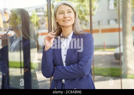Femme réussie. Portrait d'une belle femme d'affaires mûre heureuse en tenue classique tenant des lunettes, regardant de côté et souriant en se tenant debout à l'extérieur. Les gens d'affaires Banque D'Images
