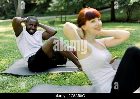 Beau homme africain allongé sur le tapis de yoga dans le parc, faisant des exercices de repos ou de croque de vélo pour renforcer les muscles de l'abs. Joli Banque D'Images