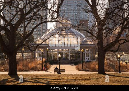 Coucher de soleil au début du printemps dans le parc des jardins Allan de Toronto avec serre devant des édifices de haute hauteur Banque D'Images