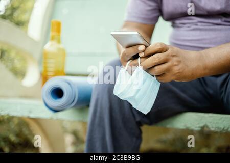 Homme utilisant le mobile avec le masque à la main au parc pendant le yoga du matin ou l'entraînement avec mat - concept de coronavirus ou Covid-19 conseils, protection ou à