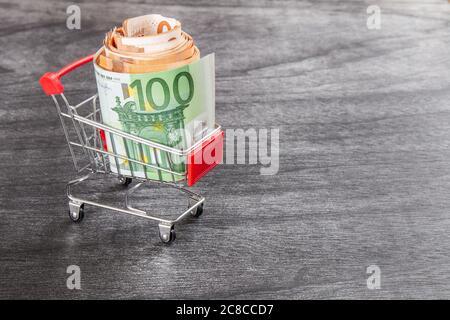 Panier plein d'argent. Shopping consept, euro de l'argent dans le panier. Panier avec des billets en euros sur gris 24. L'espace de copie pour le texte.