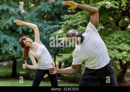 Femme caucasienne et homme africain, couple de fitness, entraînement ensemble faisant des exercices d'étirement de corps dans le parc au lever du soleil, souriant à la caméra et