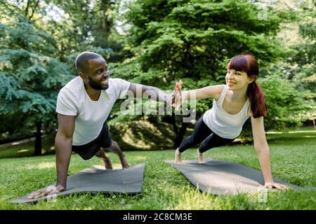 Deux amis sportifs souriants, couple multiethnique, homme africain et femme caucasienne, donnant cinq hauts l'un à l'autre, tout en faisant pousser ou s'est coulé dessus