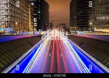 Des sentiers légers sur une route à travers le quartier européen à Bruxelles, en Belgique, la nuit. Exposition longue.