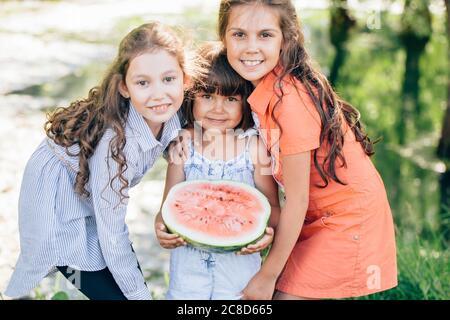 Trois jeunes filles mignons et drôles mangeant de la pastèque et faisant des visages drôles sur le parc en plein air Banque D'Images
