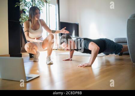 Femme motivant l'homme à faire des push-ups sur le plancher de bois franc à accueil