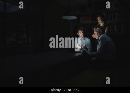 Équipe de professionnels travaillant tard au bureau, désusant des solutions