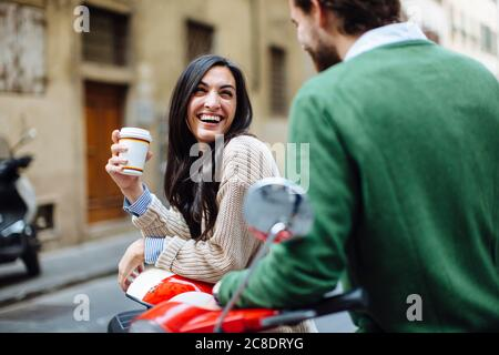 Bonne femme tenant un café en regardant le petit ami tout en s'appuyant sur Vespa