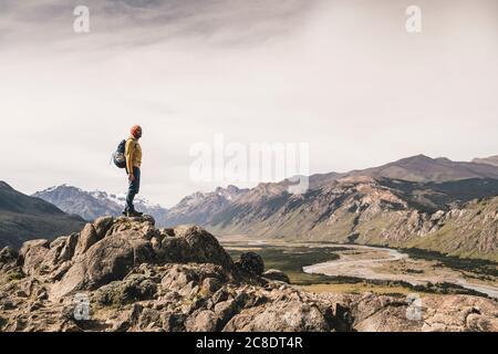 Homme mature avec sac à dos debout sur le rocher contre le ciel à Patagonia, Argentine