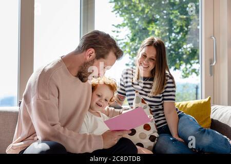 Femme souriante assise et regardant un homme lisant un livre d'images pour garçon dans la salle de séjour