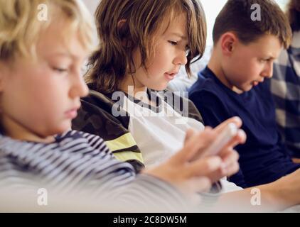 Garçon jouant à des jeux sur smartphone avec la famille en arrière-plan au salon