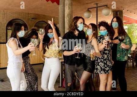 De jeunes amis dansent tout en prenant un verre au restaurant pendant le coronavirus Banque D'Images