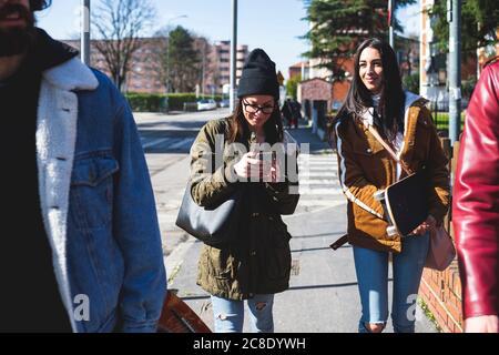 Femme utilisant un téléphone intelligent tout en marchant avec des amis sur le trottoir en ville Banque D'Images