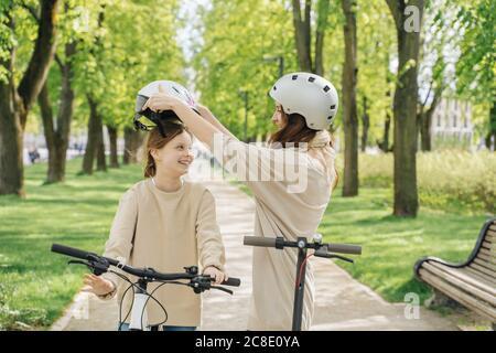 Mère portant un casque à sa fille tout en se tenant contre les arbres dans le parc