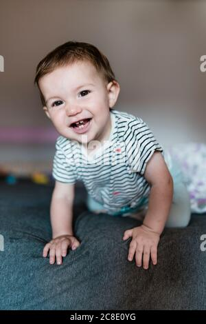 Portrait de bébé fille heureux rampant sur le lit Banque D'Images
