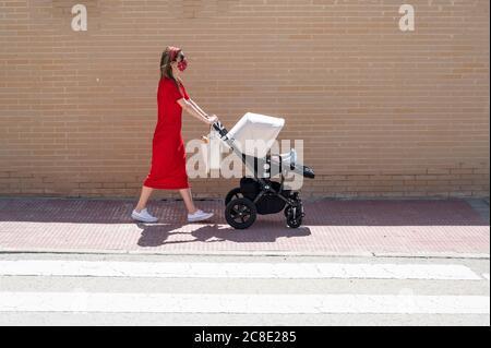 Mère portant un masque poussant son fils dans le chariot de bébé pendant la marche sur le trottoir