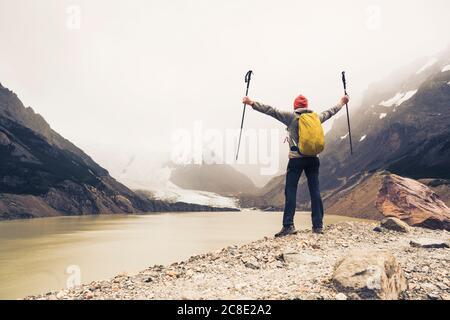 Homme aux bras étirés tenant des bâtons de randonnée debout près du lac à Patagonia, Argentine